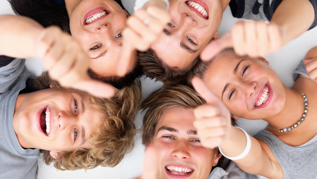 Closeup portrait of happy young friends lying on white floor showing thumbs up sign